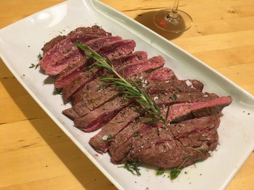 Flank Steak medium rare mit Rosmarin auf einem Teller angerichtet