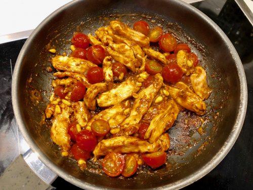 Würzmischung und Hähnchenfleisch mit Tomaten in der Pfanne